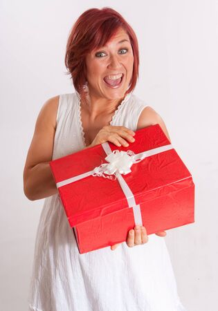 Red haired woman opening a red and white present