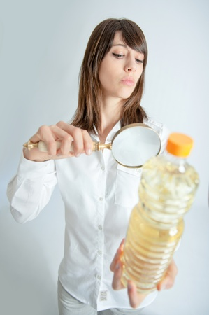 Young woman inspecting a bottle of oil with a magnifying glass