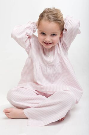 nighttimes:  Cute little blonde girl in her pajamas sitting on the floor arranging her hair  Stock Photo