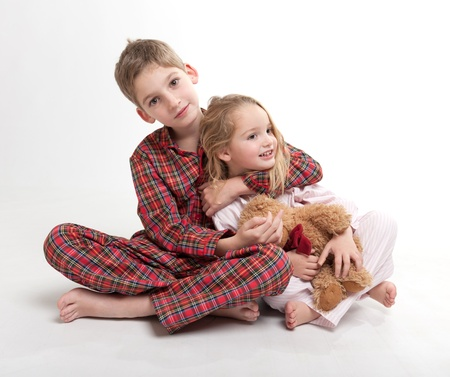 pajama:  Little boy and girl in their pajamas with a teddy bear
