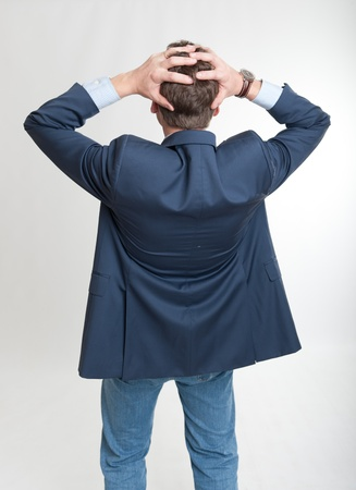 desperately:   Rear view of a man holding his head in a desperate gesture   Stock Photo