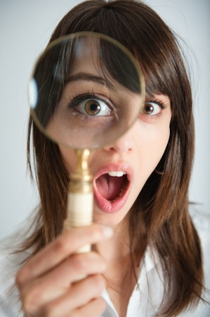 woman searching:   Portrait of a young woman looking at the camera through a magnifying glass with a shocked expression    Stock Photo