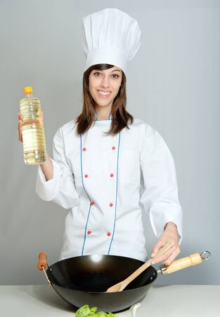 Young chef in a neutral background with a wok and a bottle of oil photo