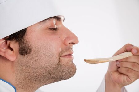 delightfully:  Male cook delightfully smelling the contents of a wooden spoon