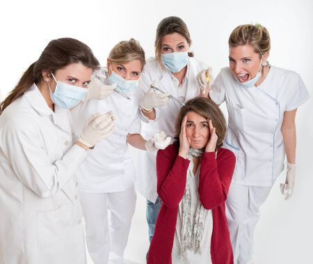 A woman on her knees surrounded by an aggressive group of female dentists   Stock Photo - 11406684
