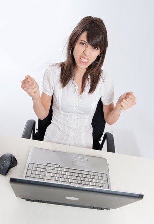 business obstacle:   Young woman sitting at her desk with her laptop with a desperate expression