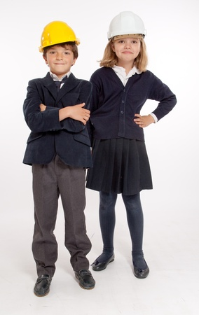 Young boy and girl in school uniforms wearing safety helmets