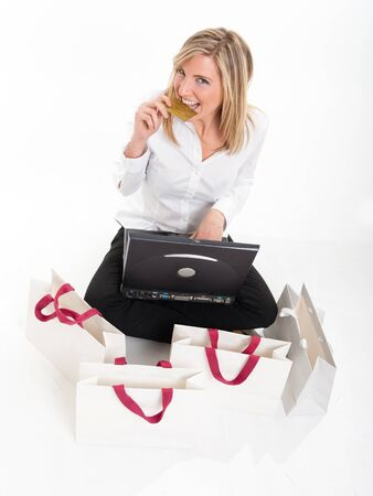 Happy young blonde biting her credit card sitting in front of a laptop surrounded by shopping bags   Stock Photo - 11406669