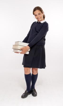Schoolgirl carrying three heavy books  photo