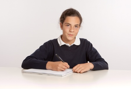 Serious schoolgirl writing on a block