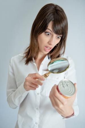 Scioccato giovane donna di ispezione di una nutrizione lattine etichetta con una lente d'ingrandimento