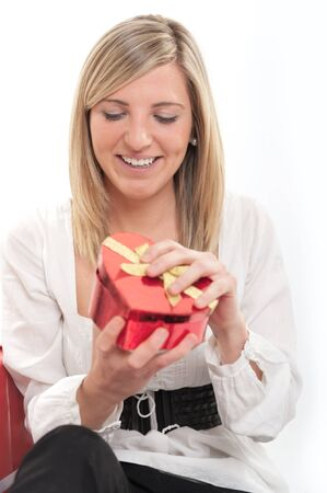 Cute young woman opening a heart shaped box   photo