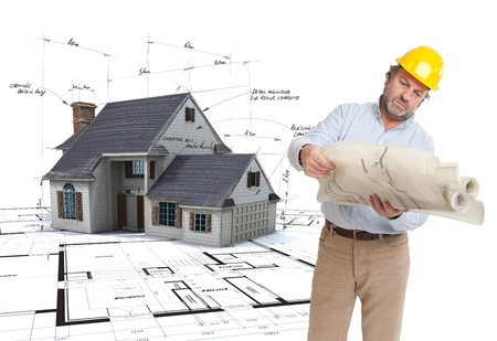 corrections:  Architect looking at his plans with a House mock-up on top of blueprints with pen notes and corrections  Stock Photo