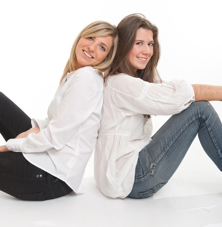 best friends girls:   Two young female friends leaning on each other   Stock Photo