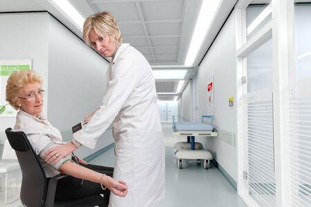 paciente en camilla: Médico comprobar una presión arterial ladys en un interior del hospital