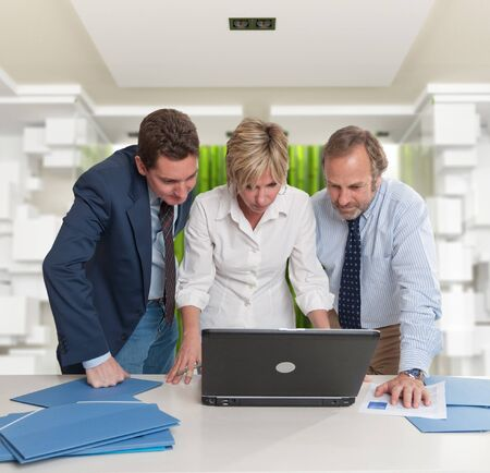 Three standing business people looking at a laptop screen in a modern interior  photo