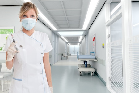 Attractive blonde female dentist holding a syringe in a clinic interior   photo