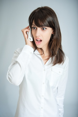 incredible:   Young brunette talking on the phone with a surprised expression  Stock Photo