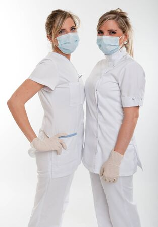dentist mask:   Two female healthcare workers with masks face to face     Stock Photo
