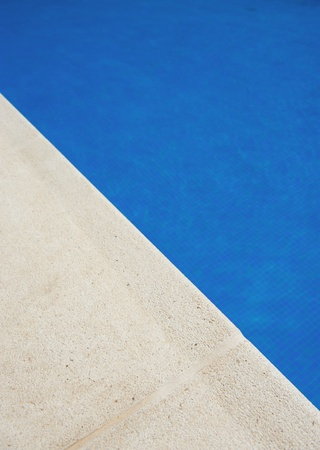 enticing:  Enticing image of blue water and stone swimming pool edge   Stock Photo