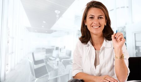 company premises: Smiling woman sitting at her desk on an office environment Stock Photo