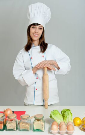 Young woman in chef�s attire using a rolling pin   photo