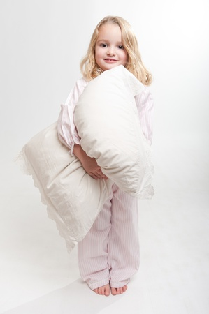Cute little blonde girl in her pajamas holding a pillow  photo