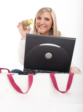 Exstatic young blond woman holding a credit card in front of a computer surrounded by shopping bags   photo