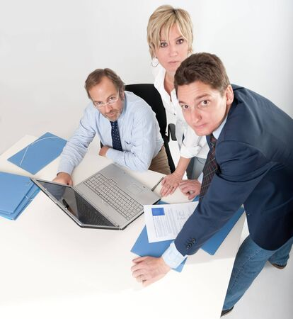 Three business people around a laptop computer  photo