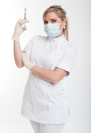 injection woman:   Attractive blonde female health worker holding a syringe