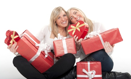 Two young sisters surrounded by gift boxes, some of them heart shaped  photo