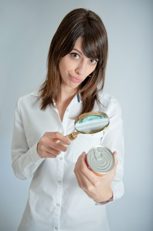food label:   Young woman inspecting a can�s nutrition label with a magnifying glass   Stock Photo