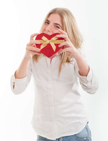 Young teenage girl happily holding a heart shaped box Stock Photo - 12125334