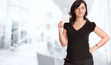 cor: Woman presenting a blank sign in a corporate background