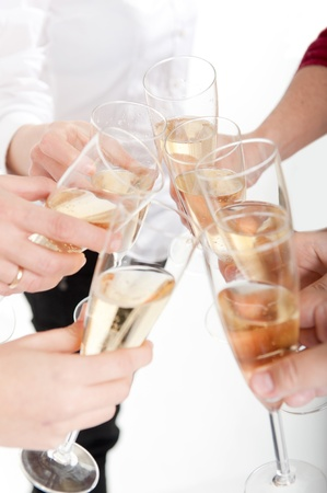 champagne toast:  Seven hands raising champagne flutes on a toast