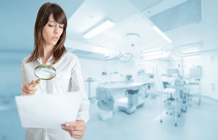 operating room: Young woman at the hospital examining a document with a magnifying glass