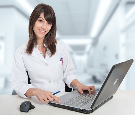 medic: Young female hospital administrative in a desk at the hospital hall Stock Photo