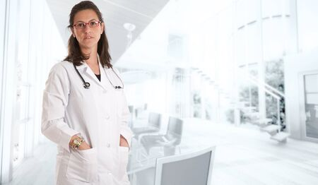 company premises: Woman with lab coat and stethoscope  in a business environment Stock Photo