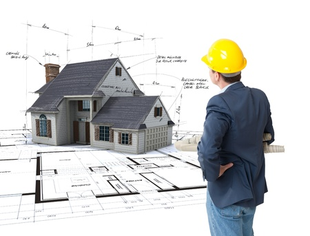 Architect looking at House mock-up on top of blueprints with pen notes and corrections  Redakční