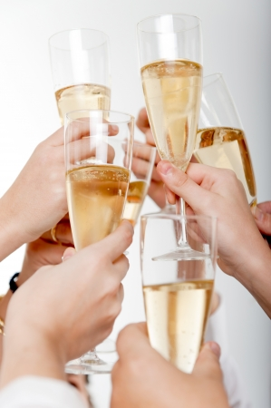 toast:  Seven hands raising champagne flutes on a toast