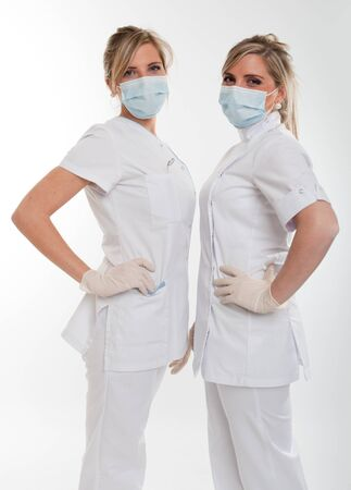 Two young female dentists posing with uniform and mask   photo