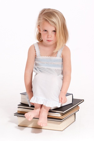 Sulking little blonde girl in a nightdress sitting on a pile of books