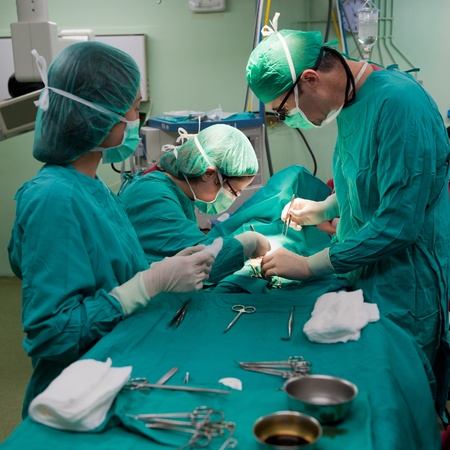 surgery table: Medical team performing surgery on a young patient