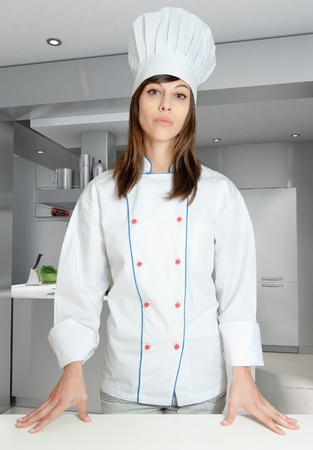 Young girl with a chef uniform in an industrial kitchen  photo