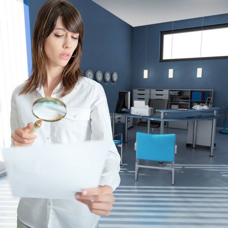 woman searching:  Young woman inspecting a document through a magnifying glass in an office  Stock Photo