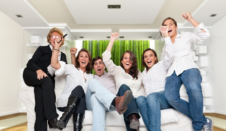A group of family members sitting in a modern interior  cheering photo