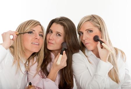 mujer maquillandose: Tres mujeres jóvenes de aplicar el maquillaje, preparándose para salir Foto de archivo