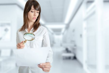 admissions: Young woman at the hospital examining a document with a magnifying glass
