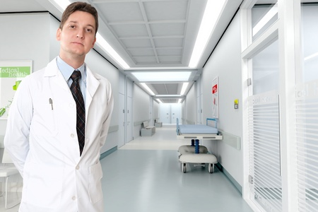 hospital corridor:   Young serious doctor standing by a hospital corridor   Stock Photo