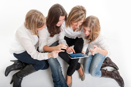 Aerial view of a group of amused girls around a pc tablet.  Please note that the logo and writing on the tablet are mine. I am attaching a property release, so no copyright issue.  Stock Photo - 13116491